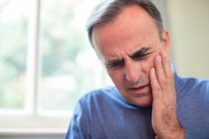 Man in pain who needs an emergency dentist in Whitinsville
