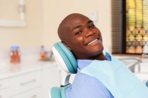 Man smiling in chair at visit with dentist in Whitinsville