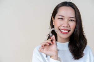 Woman holding Invisalign while smiling at the camera