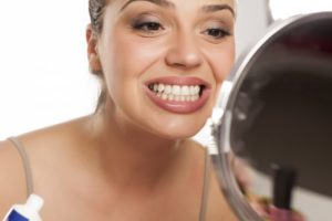Woman looking at her smile in the mirror